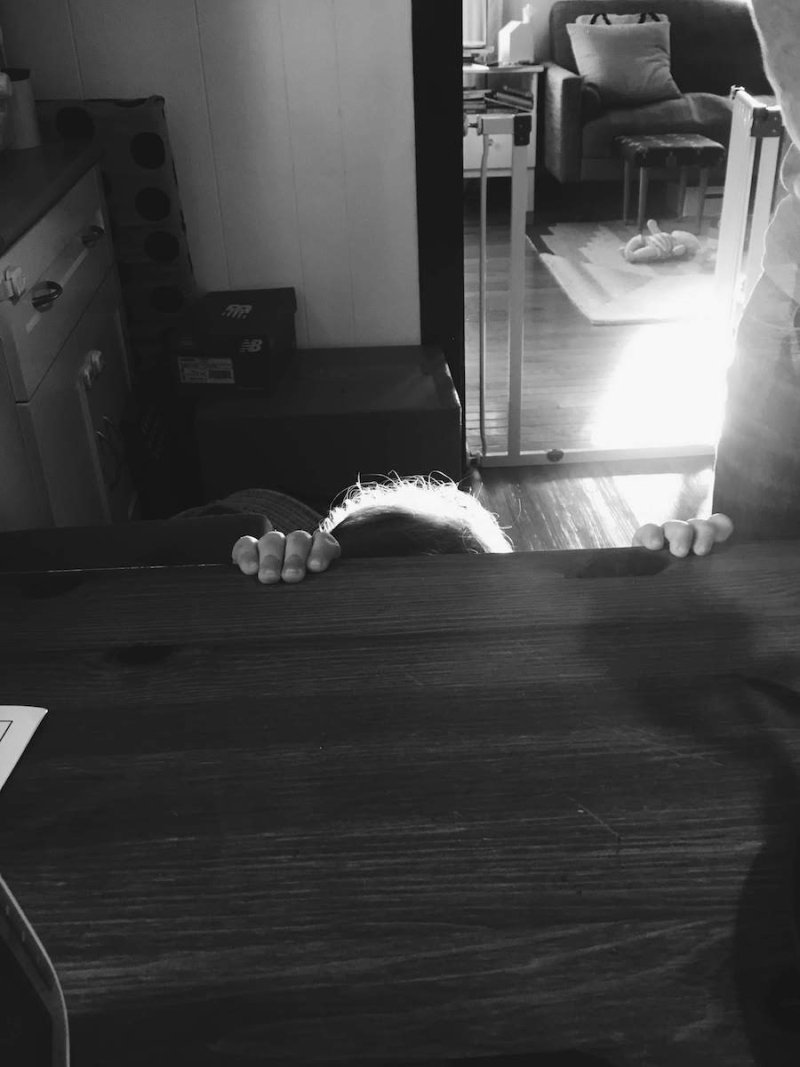 Toddler peeking over a kitchen table