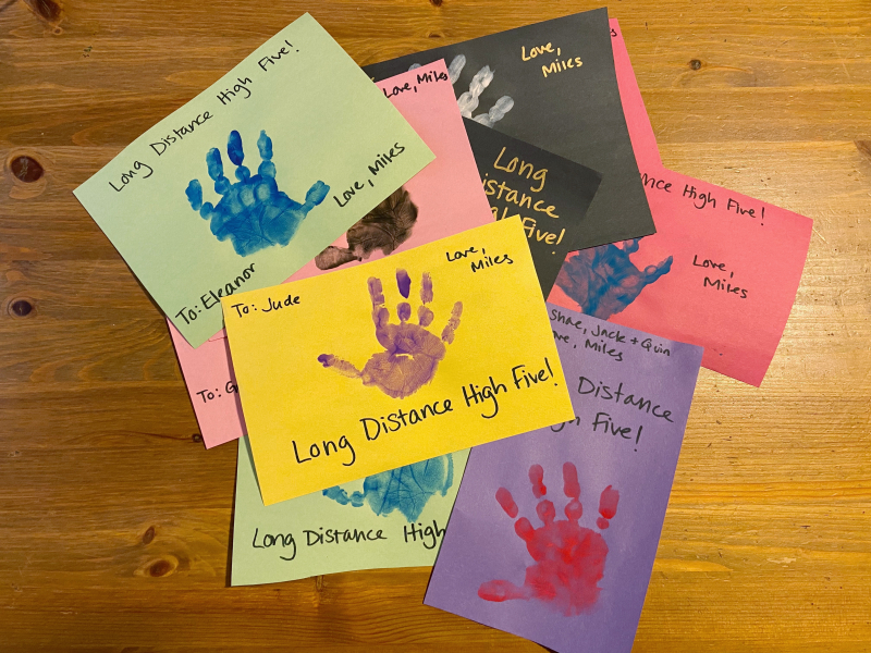 A pile of cards sits on a table. Each is a different color and has a small child's handprint and the text 'Long distance high five' on it