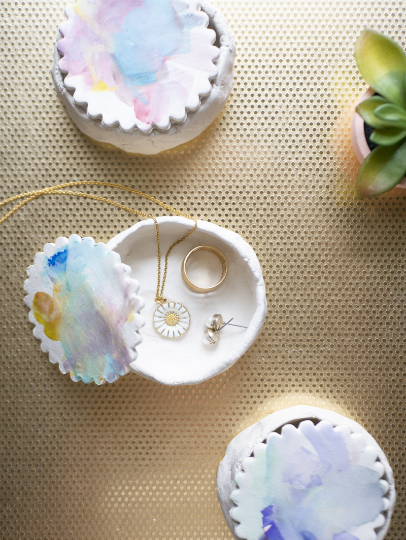 Three jewelry dishes with watercolor lids viewed from above on a gold table