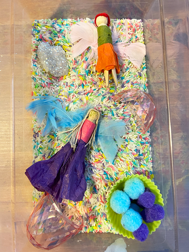 A sensory box is full of rainbow-dyed rice, sparkly gemstones, and fairies made from clothespins.