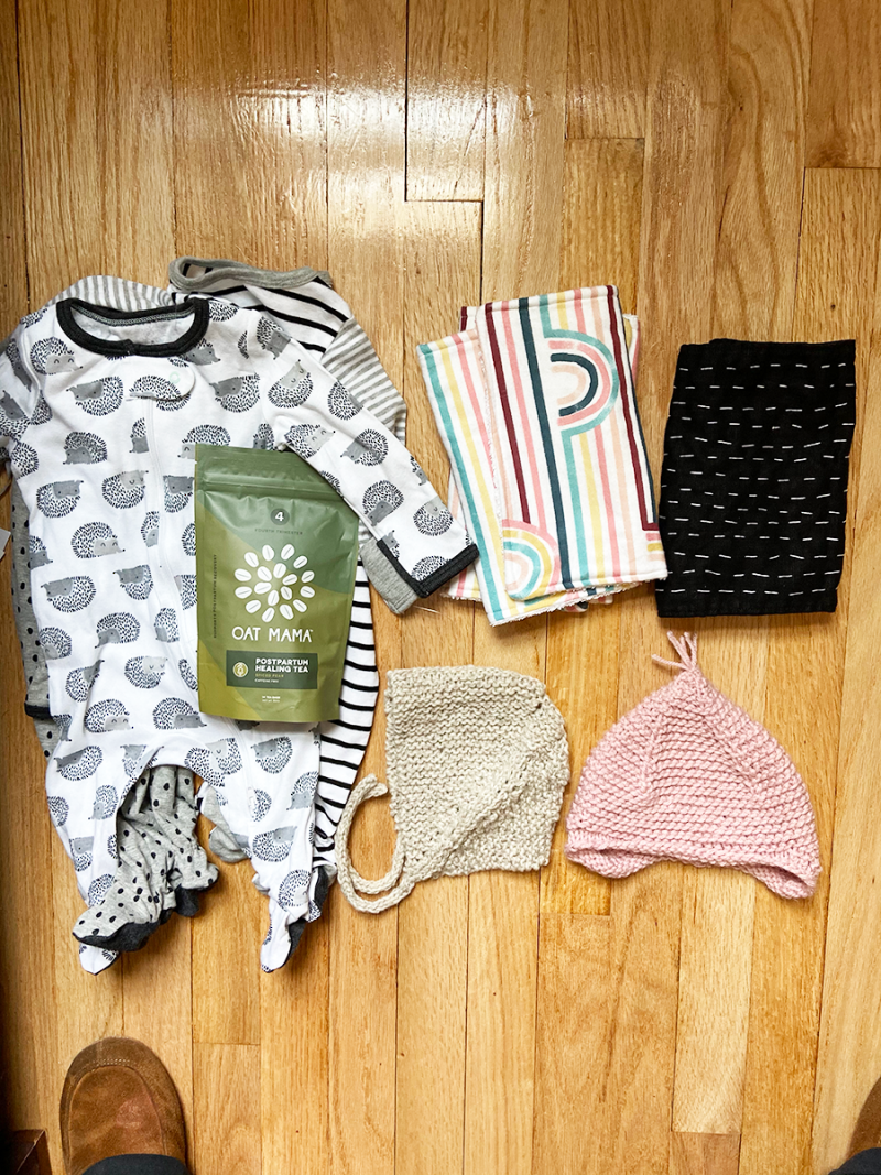 Baby gifts are displayed on a hardwood floor. There is a set of gender-neutral zip pajamas, a bag of postpartum healing tea, two hand-knitted baby hats, a pair of burp cloths with rainbows, and a black burp cloth stitched with white thread.
