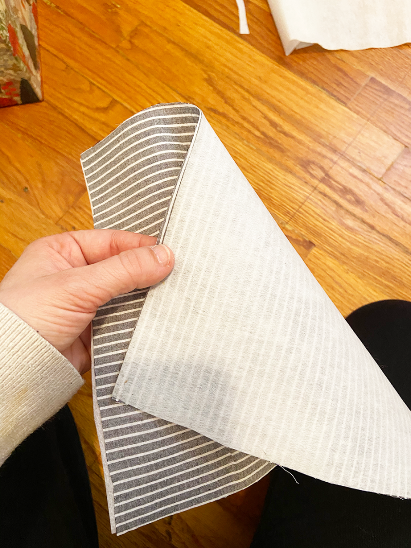 A person's left hand is holding a piece of blue and white striped fabric so that the other side is visible, where fusible interface has been attached.