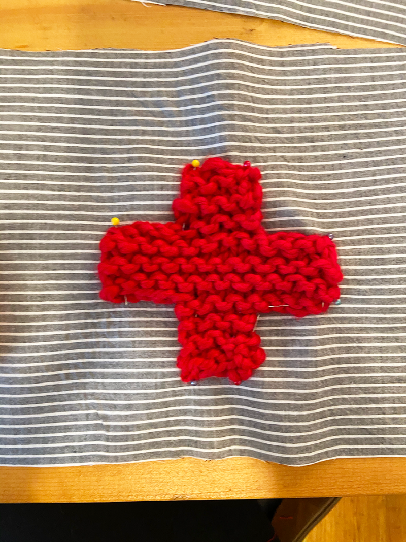 A red cross knitted with bulky yarn is pinned with straight pins to a piece of blue and white fabric