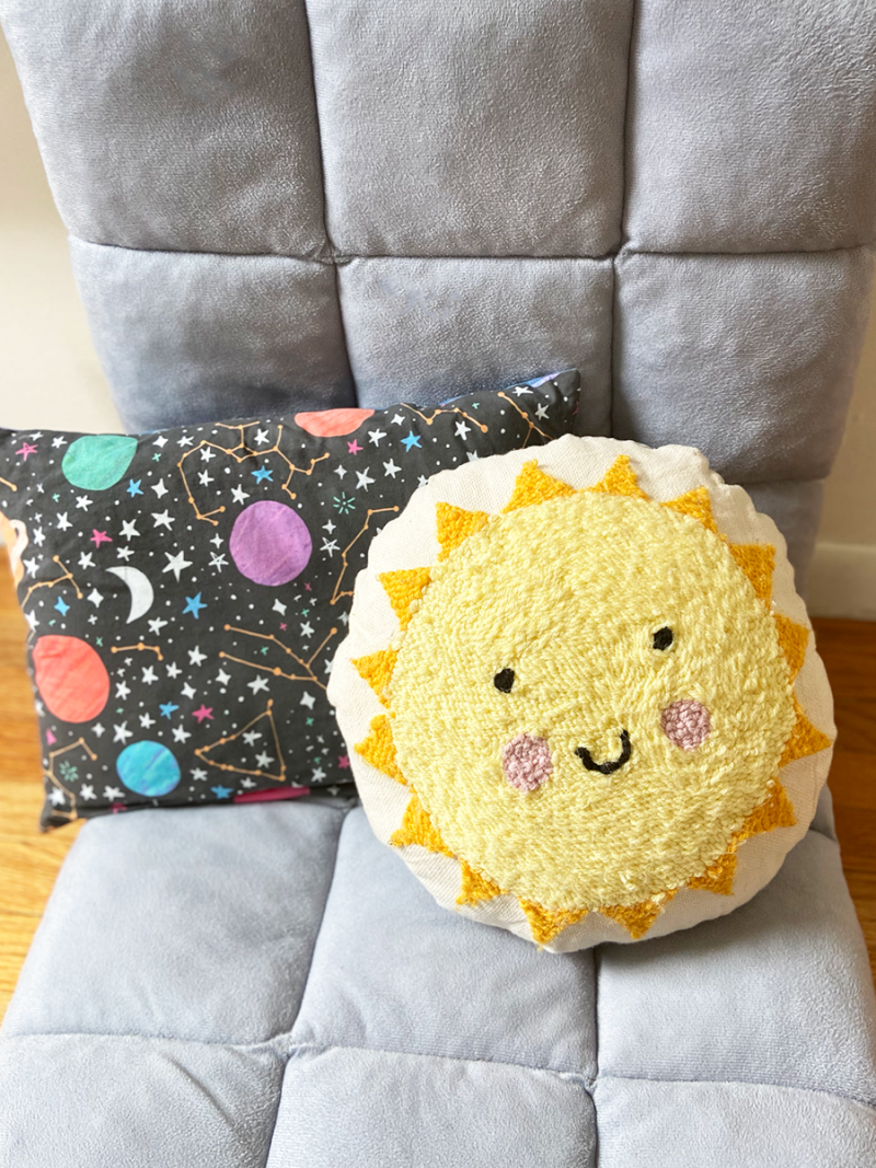 A circular pillow with the punch needle design of a yellow sun with a smiley face is on a grey fabric chair in front of a pillow with outer space constellation fabric.