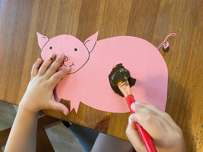A child's hands paint a pink pig with brown paint