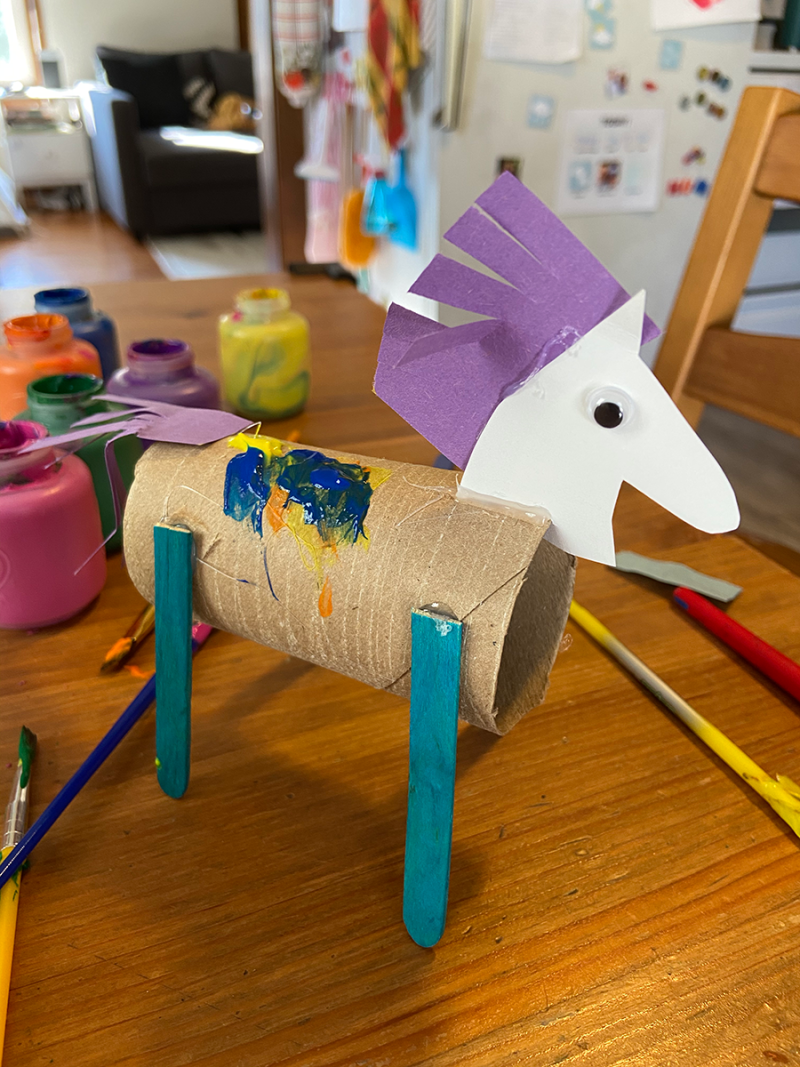 A horse toy made from a toilet paper tube is pictured on a messy kitchen table