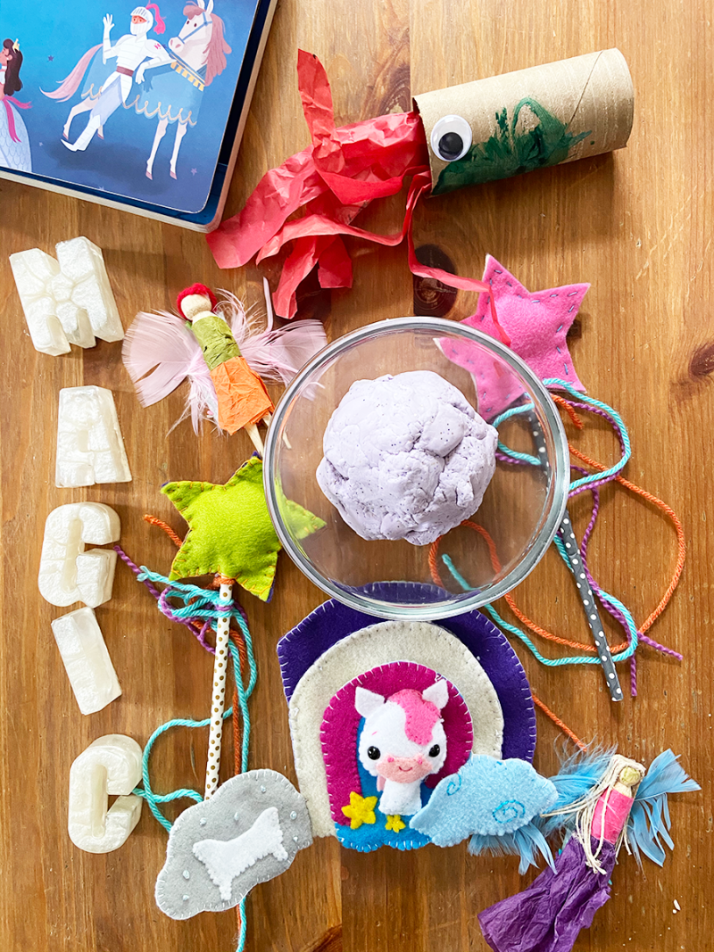 Various magic-related toys are laid out on a wooden table. These include plastic letters that spell the word magic, a felt pegasus toy, a dragon made out of a toilet paper roll, homemade playdough in a glass bowl, fairies made from clothespins, and wands made from straws.