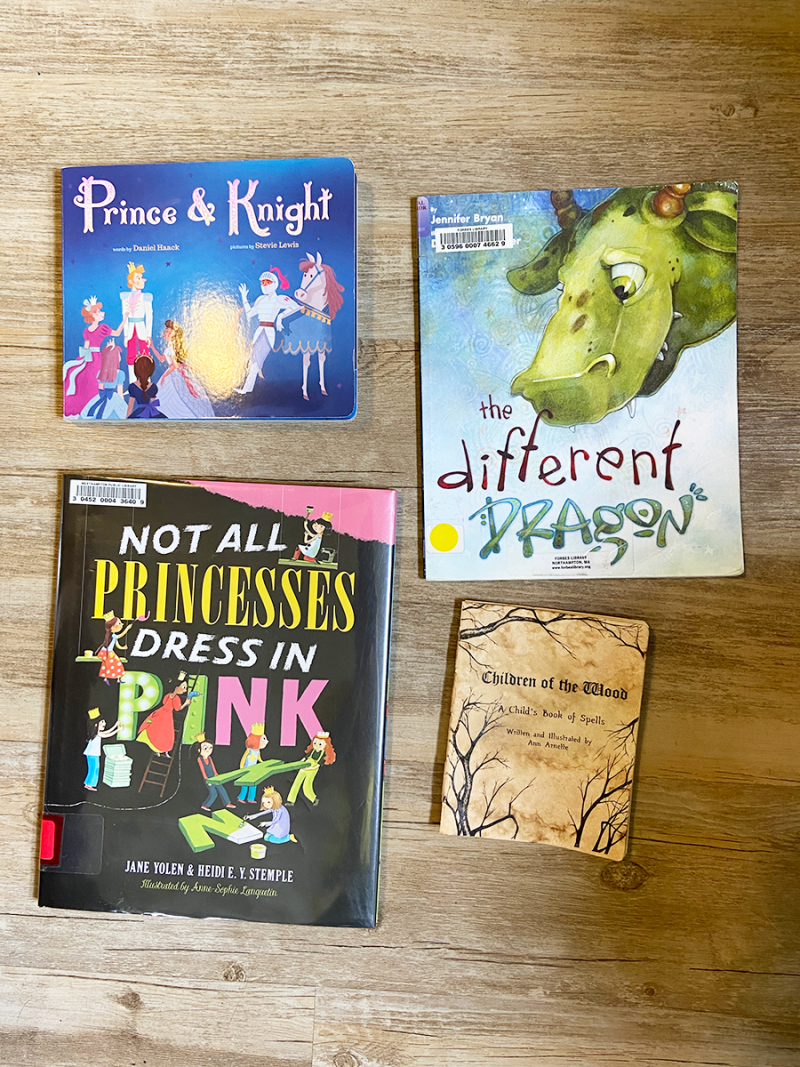Four books are on a wooden floor. Prince and Knight, the Different Dragon, Not All Princesses Dress in Pink, and Children of the Wood.