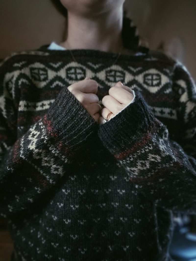 A photo of Hannah's hands. She is wearing the repaired sweater. Her hands are next to each other, displaying both the repaired and original cuff next to one another.