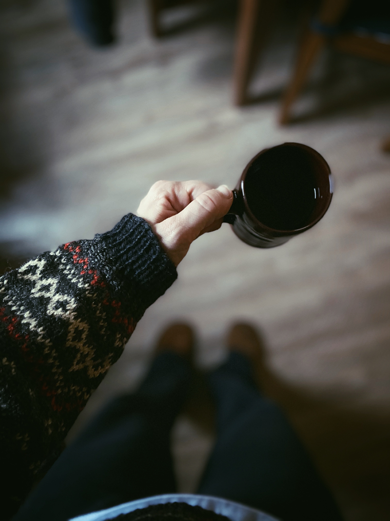 A closeup of a mug of tea held in a hand. The person is wearing the repaired sweater. The repaired cuff is visible.