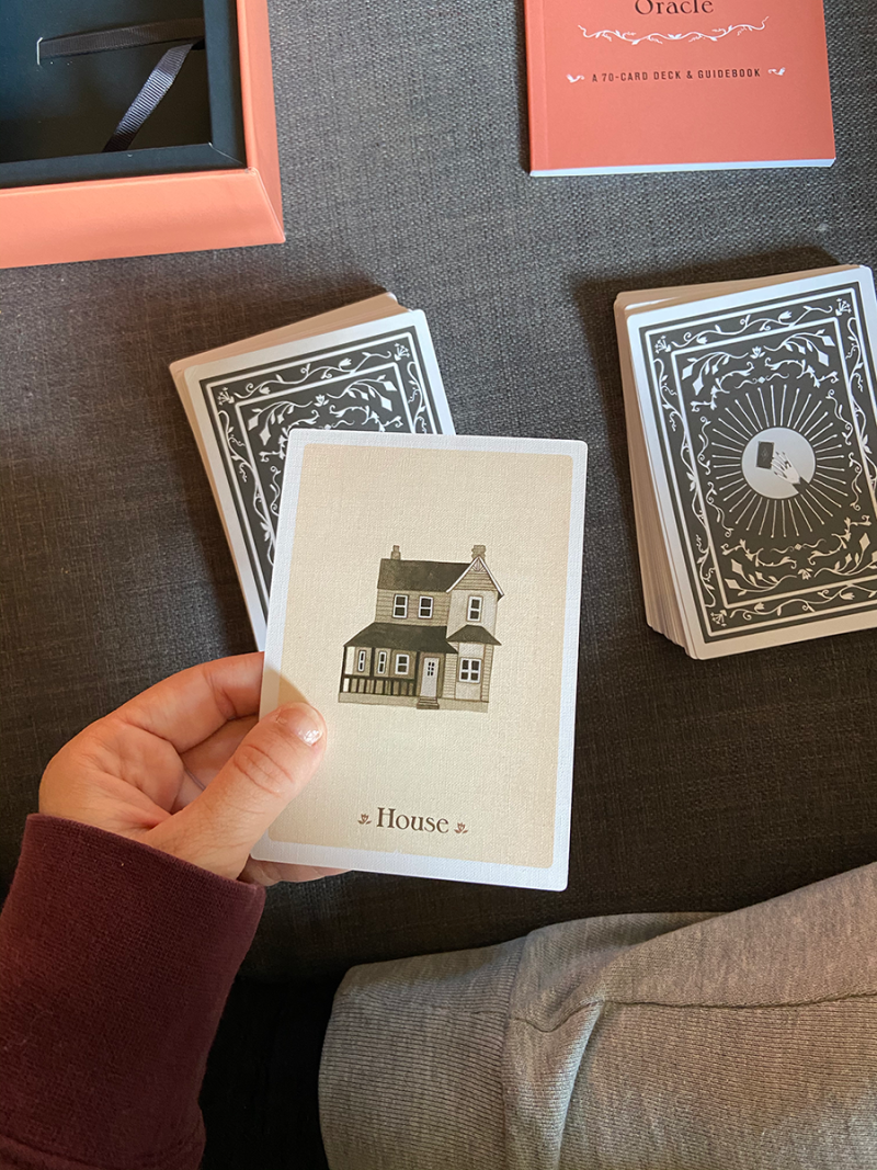 A person's hand is holding a tarot card that says House and features an illustration of a house by Goody Horan
