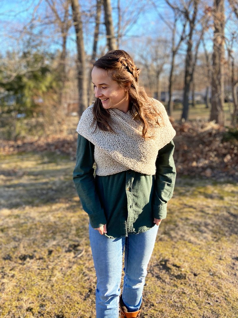 Hannah is wearing a dark green flannel shirt and a pale taupe sontag wrapped around her and tied in the back. She has a side braid and wavy hair. She is glancing down to her right with a smile on her face. She is standing in the backyard and denuded trees are in the background.