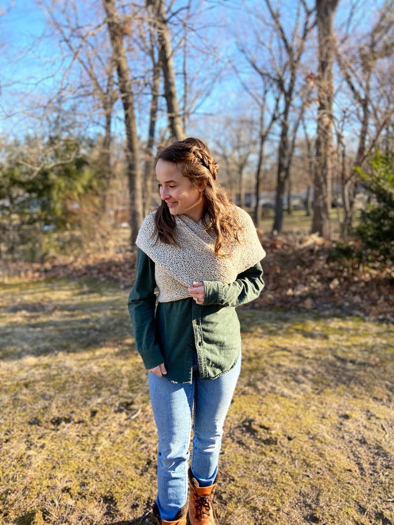 Hannah is wearing a dark green flannel shirt and a pale taupe sontag wrapped around her and tied in the back. She is holding the shawl with her right hand. She has a side braid and wavy hair. She is glancing down to her right with a smile on her face. She is standing in the backyard and denuded trees are in the background.