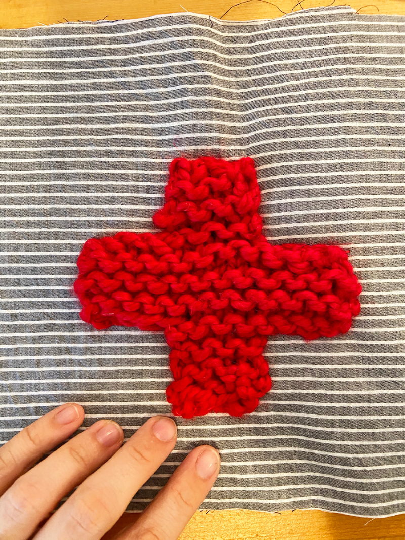 A red cross knitted with bulky yarn is photographed on blue and white fabric. The fingers of a person's left hand are visible in the picture.