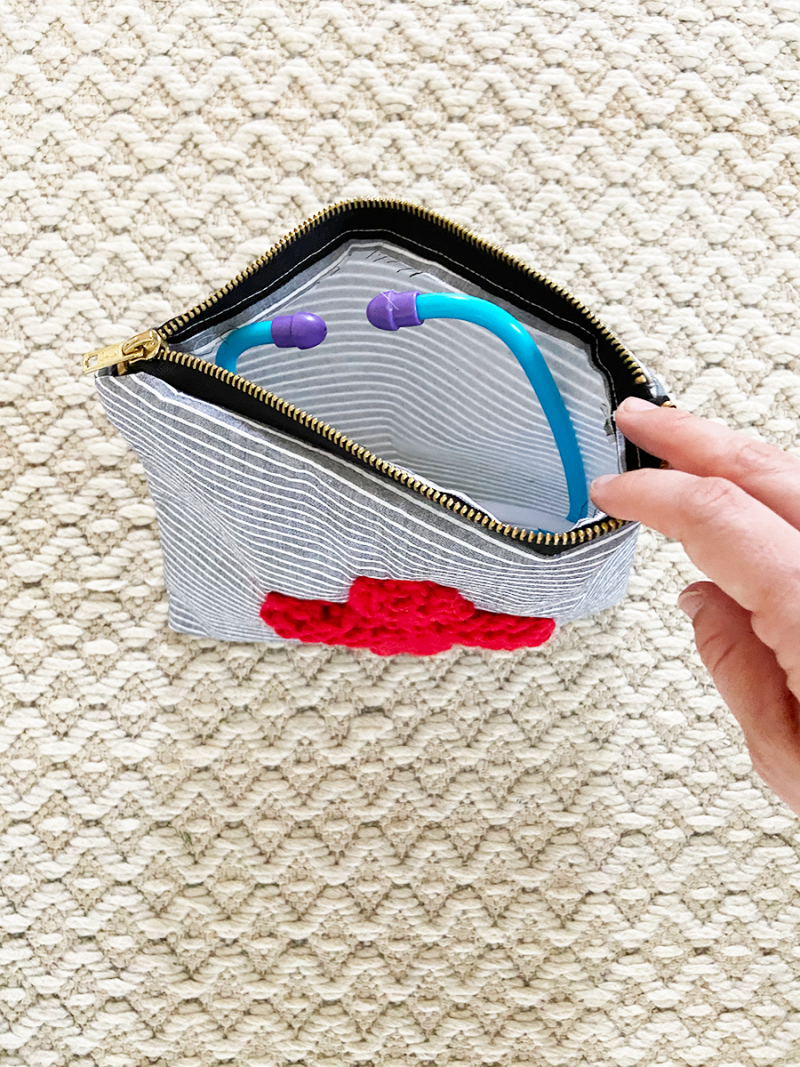 Photographed from above, a handmade zippered pouch is open, revealing its contents to be plastic children's medical toys. The pouch was sewn with blue and white striped fabric, and a red cross knitted with bulky yarn was sewn onto the front.