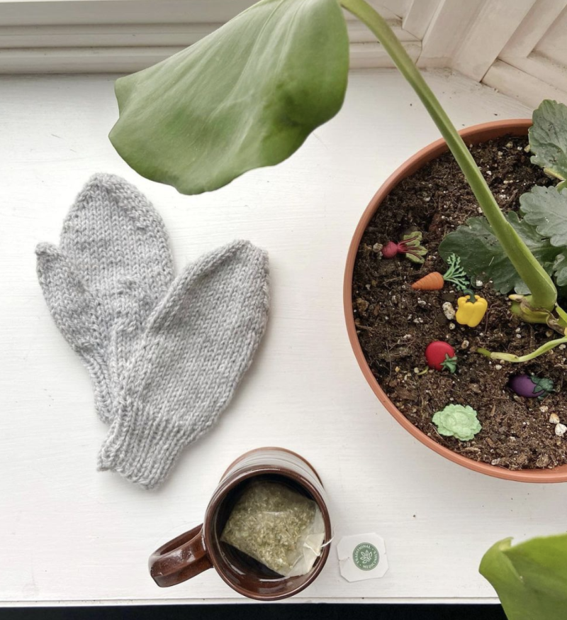 A pair of hand knit child size mittens are arranged on a wide white windowsill. They are knitted with light grey worsted yarn. Next to the mittens is a potted plant with wide green leaves. In the soil of the plant, a child has arranged buttons shaped like vegetables. A cup of tea is also steeping on the windowsill, in a brown ceramic mug.