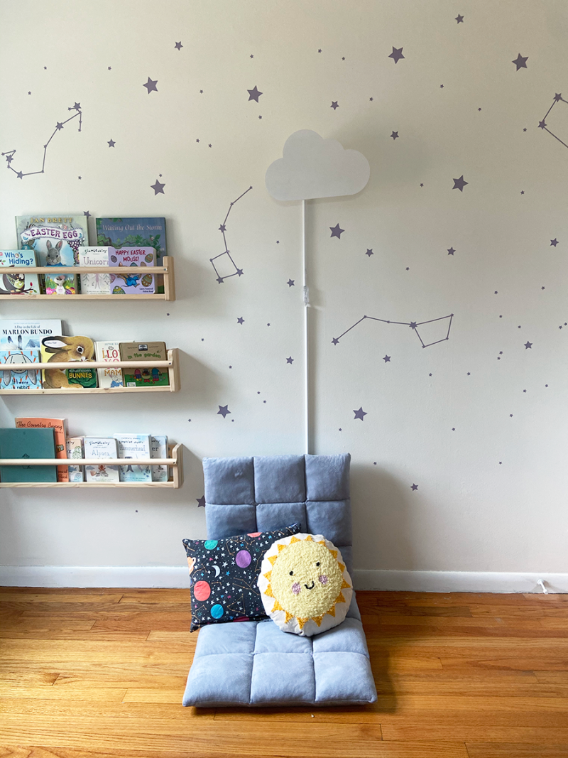 A children's room with white walls. A low grey fabric chair has two pillows on it: one with outer space fabric and one that is a sun design in a punch needle pattern. Three bookshelves are on the wall. A cloud lamp is attached to the wall above the chair, and purple star stickers form constellations on the wall.