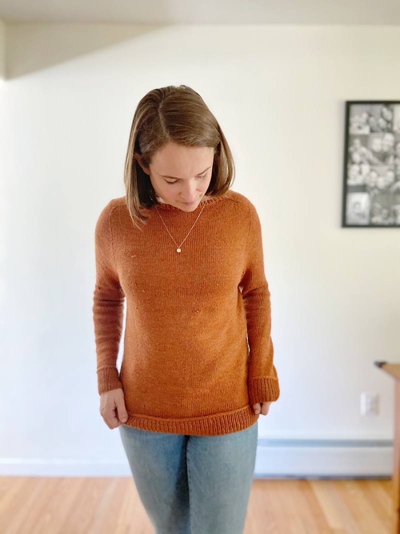 Hannah is wearing a rust-colored hand knit pullover sweater and standing in front of a white wall. She is glancing down.