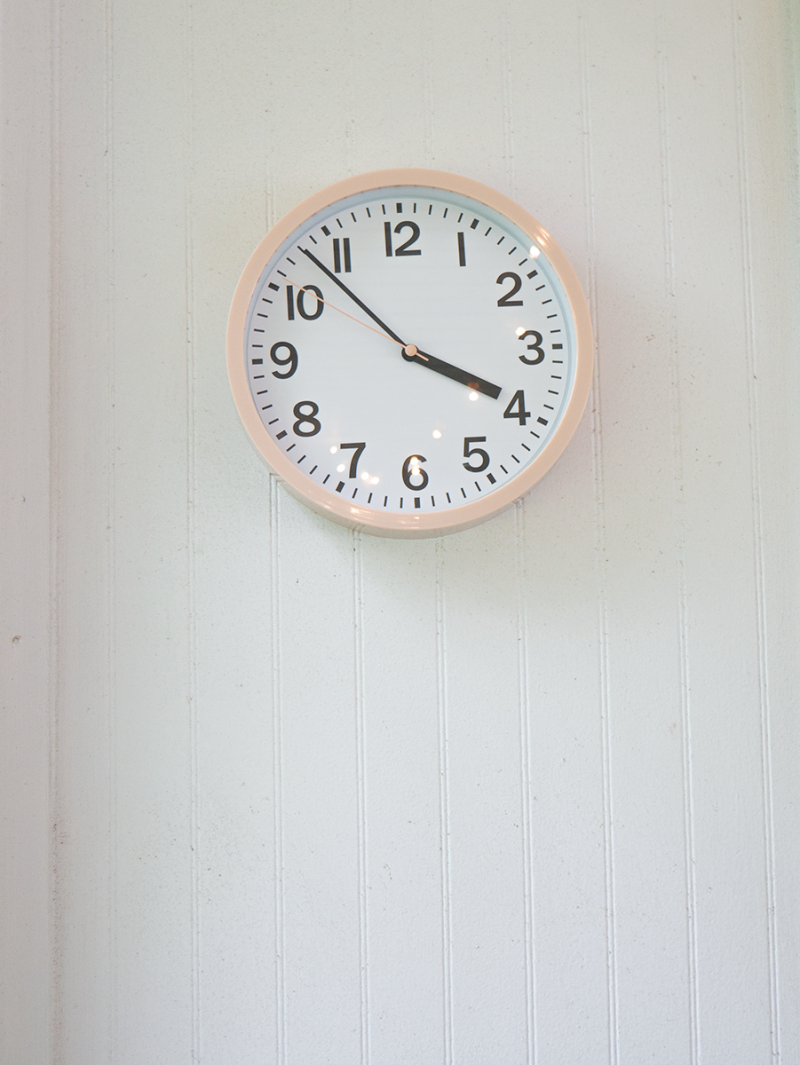 A pink clock hangs on a white wall.