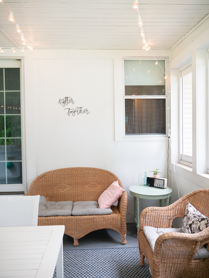 An enclosed porch with white walls. There is a wicker couch with grey cushions, and string lights hanging from the ceiling.