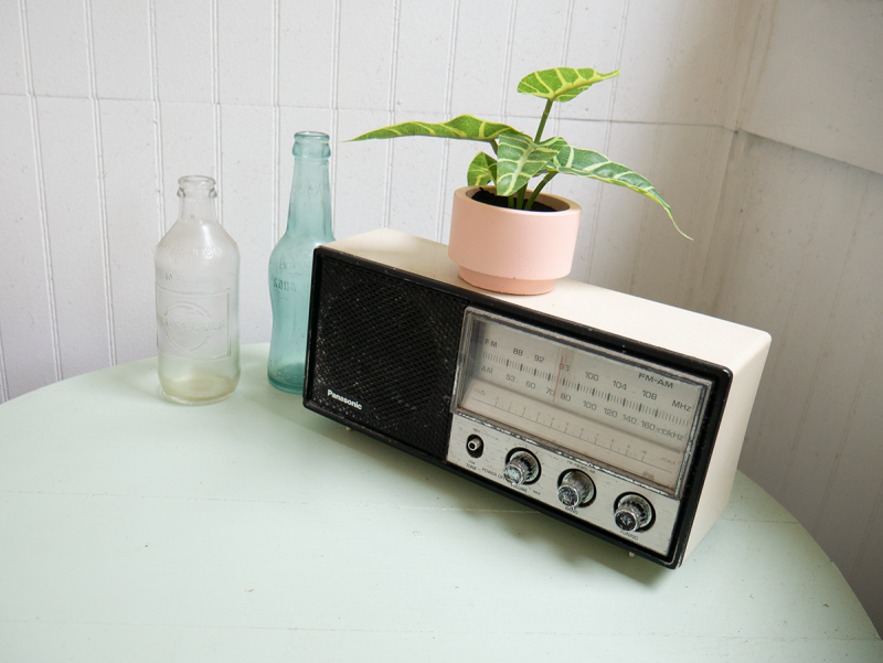 A vintage radio sits on a pale green wooden table.