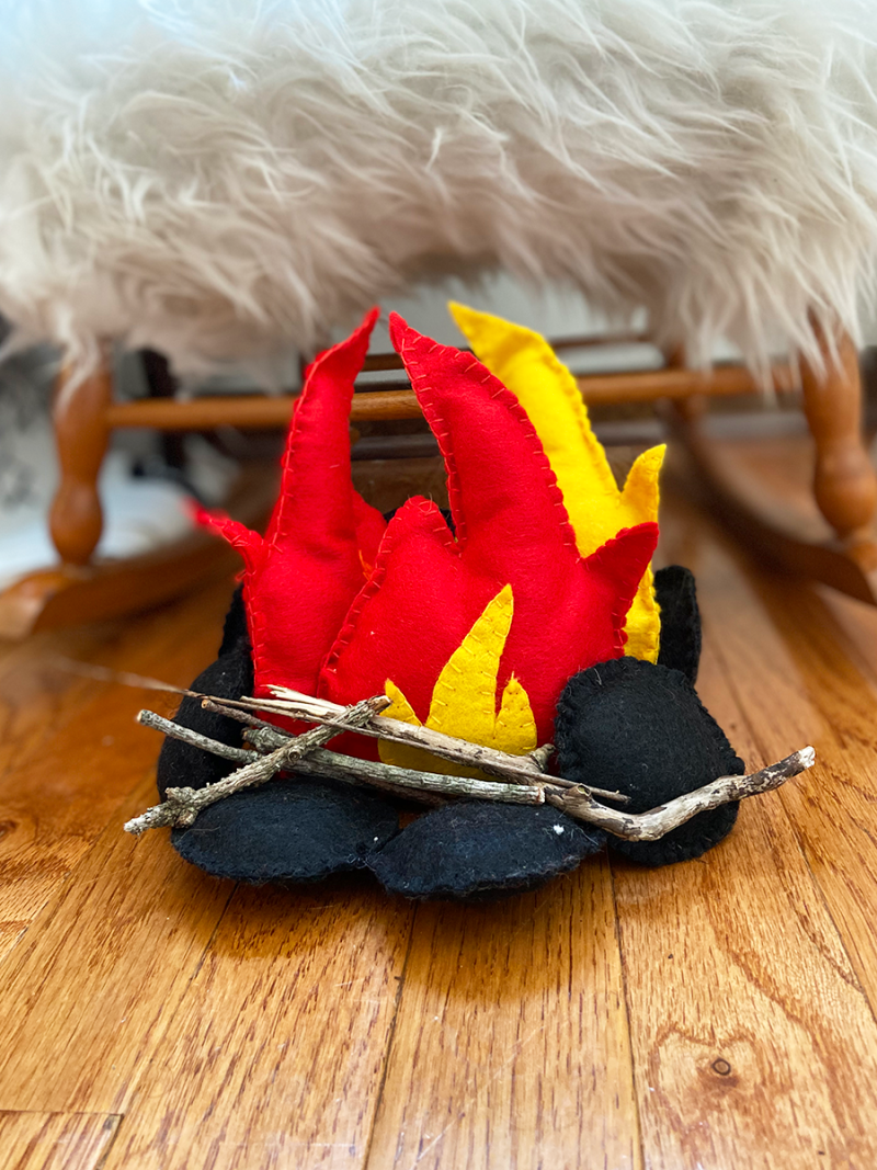 A plush campfire toy is arranged on a wooden floor