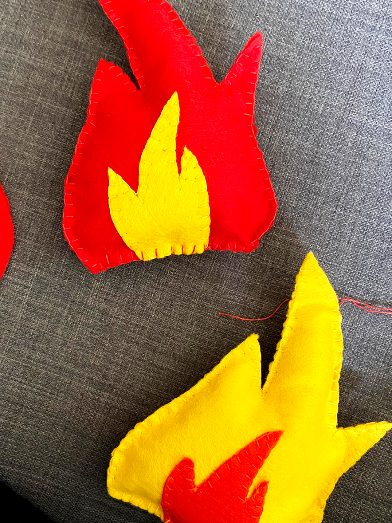 Felt flame-shaped pieces are being stitched together