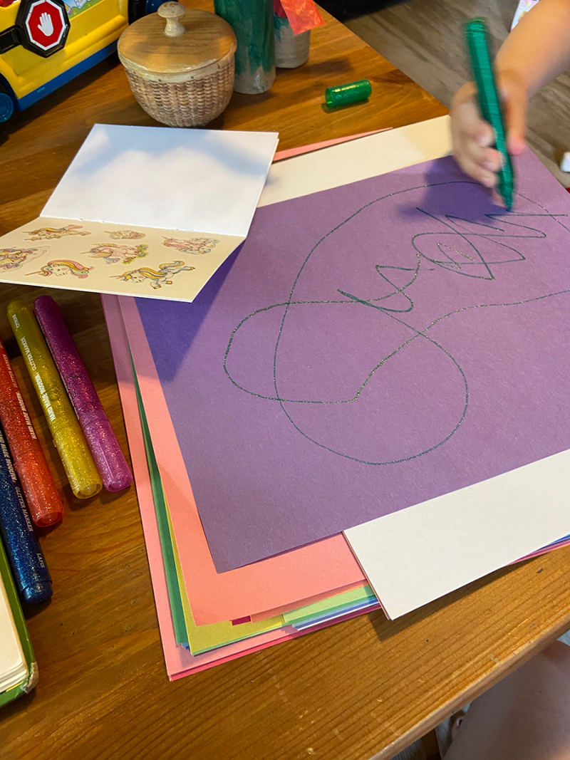 A pile of construction paper on a table with a purple piece on top. A toddler's hand is visible drawing in circles with a sparkly green pen. Unicorn stickers are nearby.
