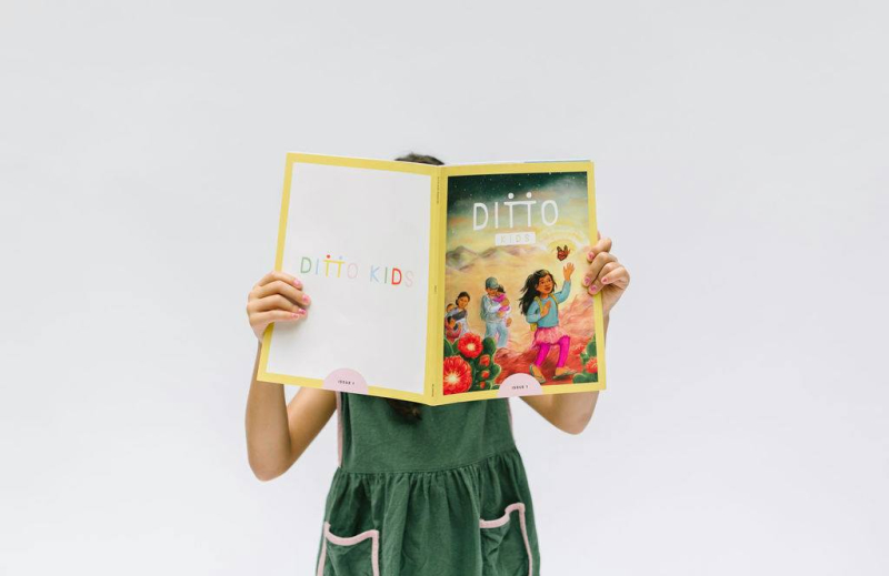 A child wearing a green dress with pockets is holding an open issue of Ditto Kids magazine over their face.