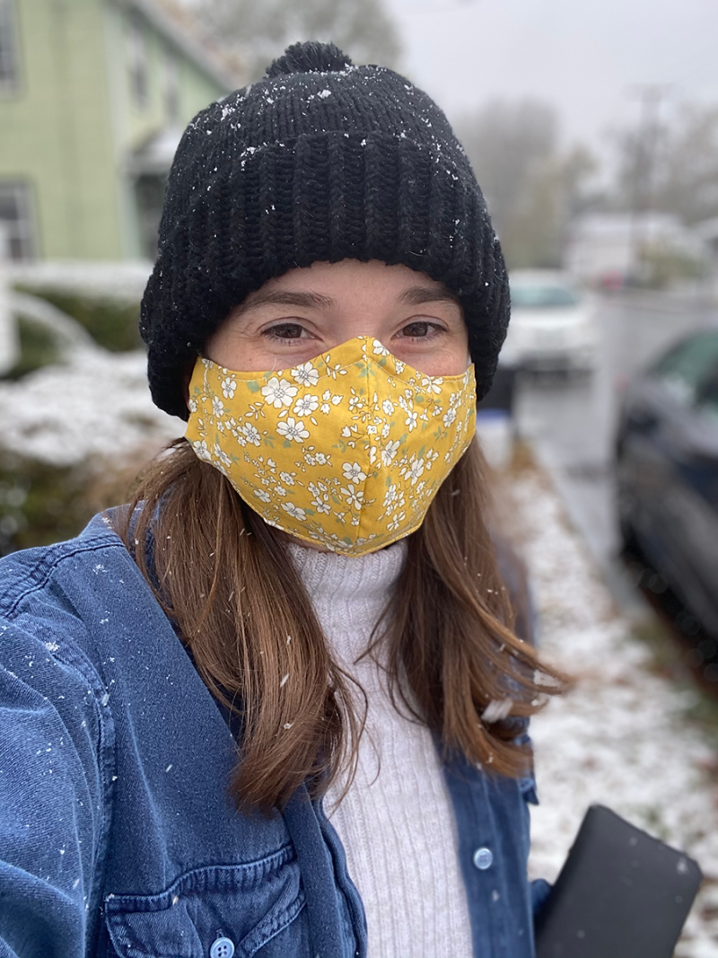 Hannah is standing outside. Snowflakes are caught in her medium-length brown hair. She is wearing a black knit hat and a fabric face mask printed with a yellow floral pattern.