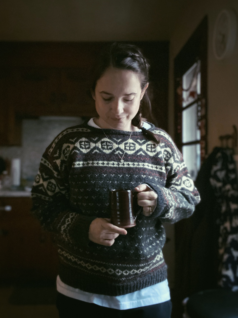 Hannah is wearing a grey, white, and red hand knit sweater and is holding a mug of tea.