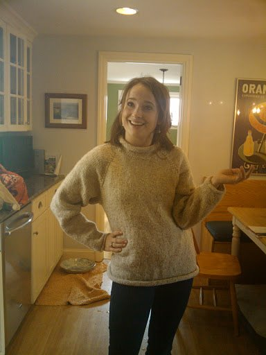 A younger Hannah is posing standing in a cluttered kitchen and wearing a hand knitted pale tan sweater with a small turtleneck.