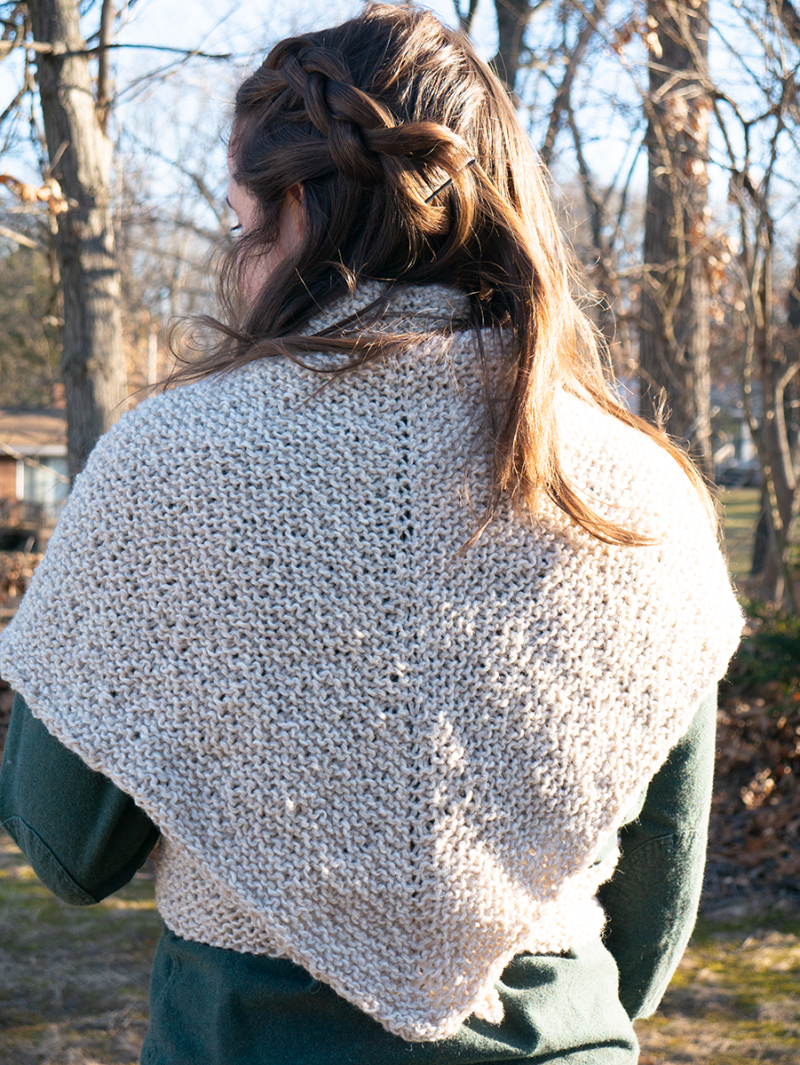 Hannah is photographed from the back. Her brown hair is in a side braid. The rest of it is wavy. She is wearing a pale tan sontag shawl wrapped around her shoulders. The shawl comes to a point at her waist.