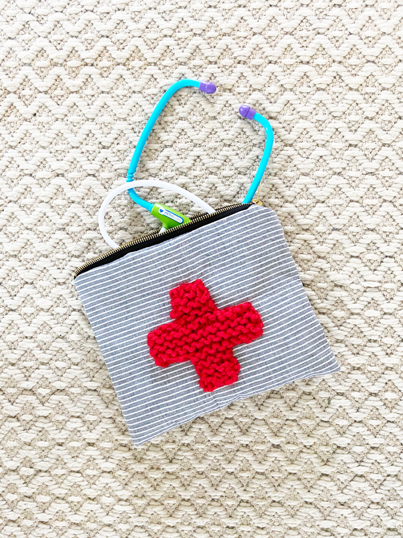 A handmade zippered pouch is on a white woven rug. It is made of blue and white striped fabric, and there is a red knitted cross sewn to the front. The zippered top is open, and children's doctor toys are emerging from the bag.