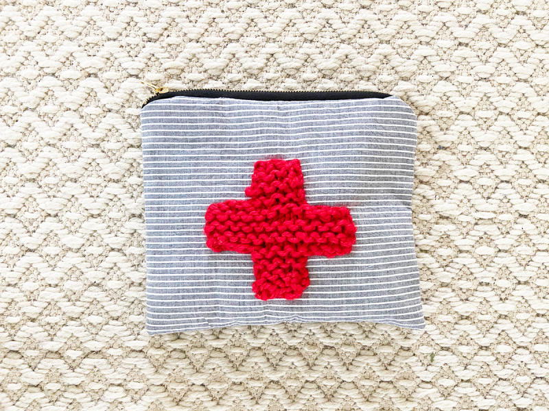A handmade zippered pouch is on a white woven rug. The pouch is made with blue and white striped fabric, and has a red cross knitted with bulky yarn attached to the front.
