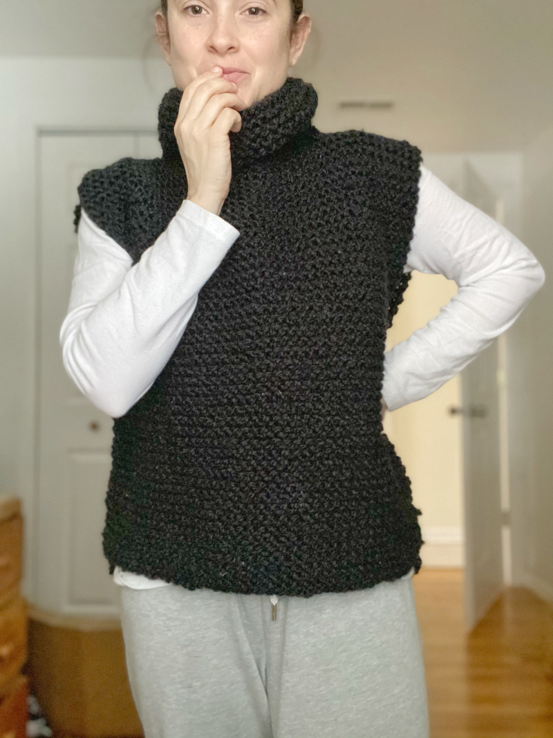 Hannah is wearing a handknit black turtleneck sweater vest over a white long sleeved shirt. She is standing in a room with light wooden floors and white walls. She is also wearing grey sweatpants.