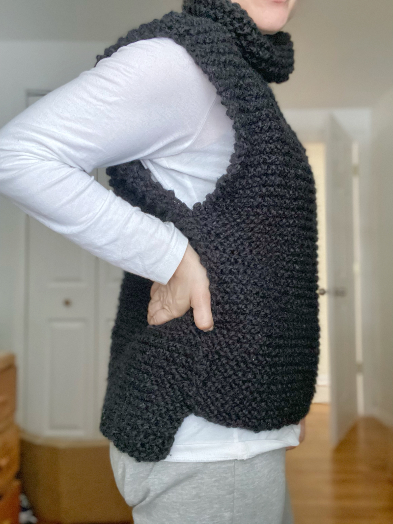 Hannah is standing to the side with her hands on her hips. She is wearing a hand knit black turtleneck sweater vest over a white long sleeved shirt.