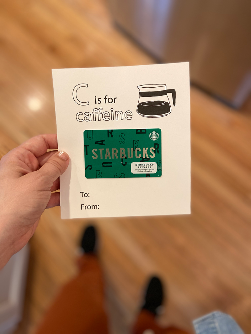 A white person's hand is holding a piece of white cardstock. On the paper are the words C is for Caffeine, to, from, with a line drawing of a coffee pot. A green Starbucks gift card has been taped in the middle.