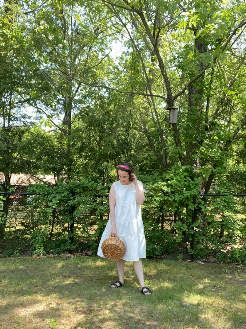 Hannah is standing in her backyard wearing a white cotton tiered dress.