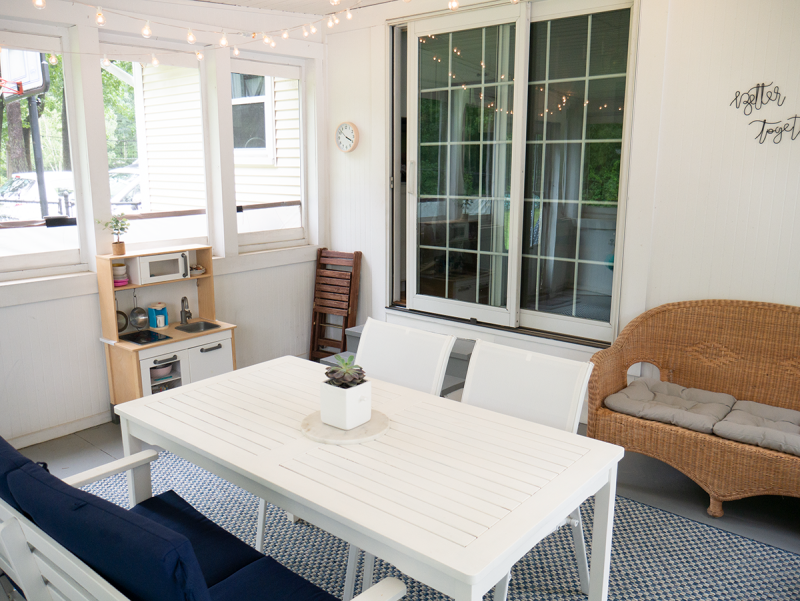 An enclosed porch featuring a white table with white chairs, a child's play kitchen, and folding chairs in the corner.