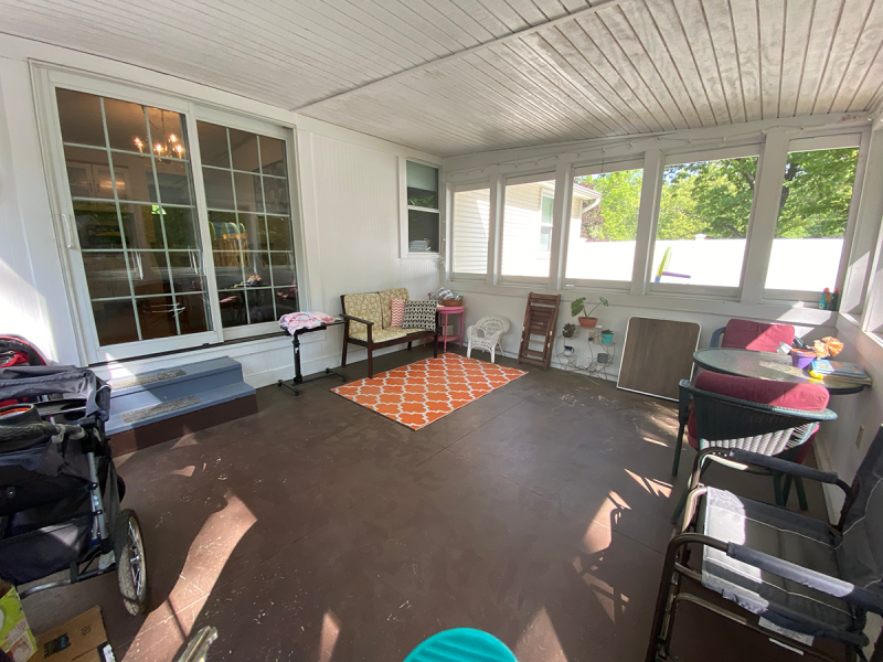A cluttered back porch with brown floor, random furniture, and a stroller.