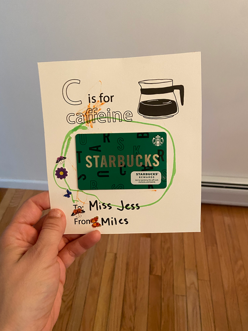 A white person's hand is holding a piece of white cardstock. On the paper are the words C is for Caffeine, to Miss Jess, from Miles, with a line drawing of a coffee pot. A toddler has scribbled on the paper with markers and added butterfly stickers. A green Starbucks gift card has been taped in the middle.