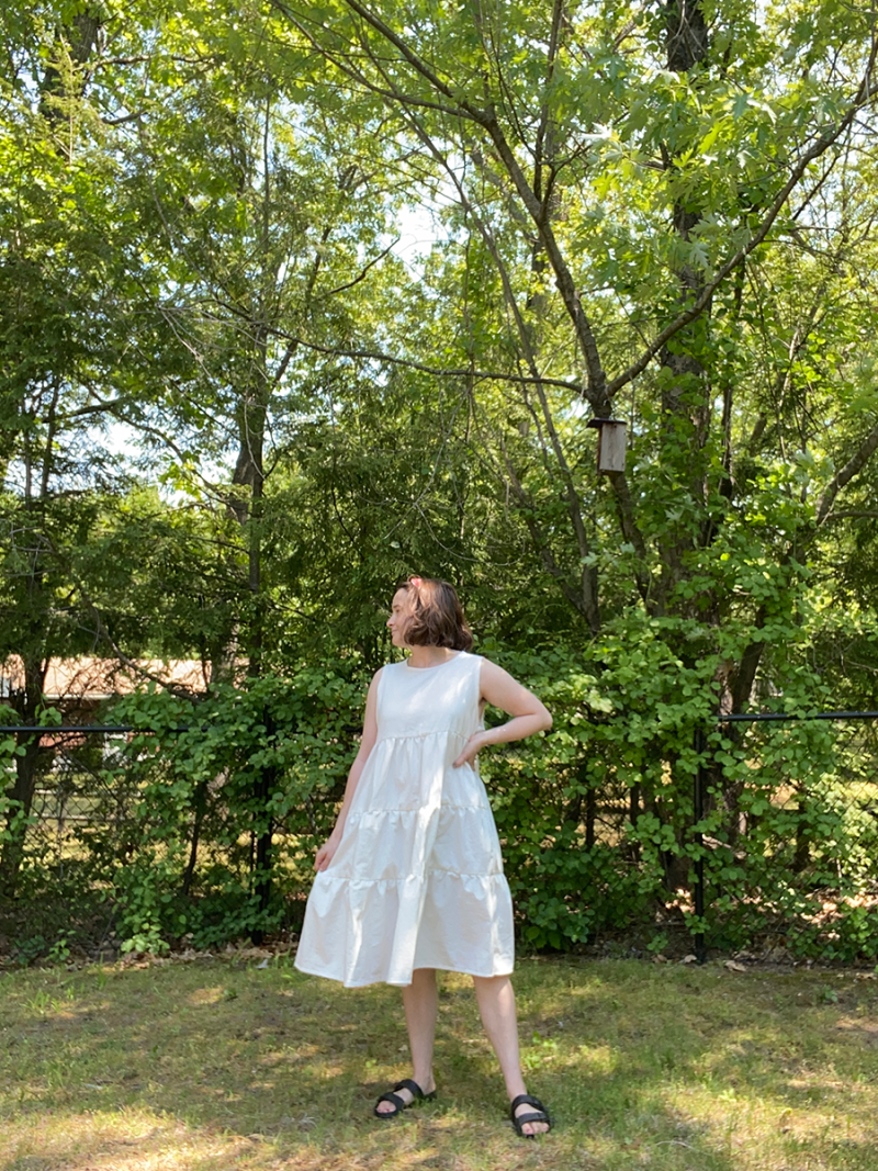 Hannah is standing in her backyard wearing a white tiered cotton dress