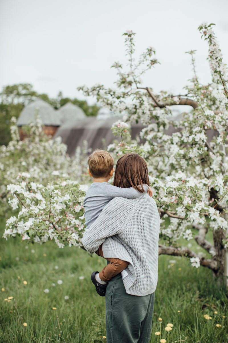 A mother with shoulder-length brown hair wearing a grey knit sweater over a green jumpsuit is holding her toddler son on her left hip in an apple orchard. His arms are around her neck. They are both turned away from the camera.