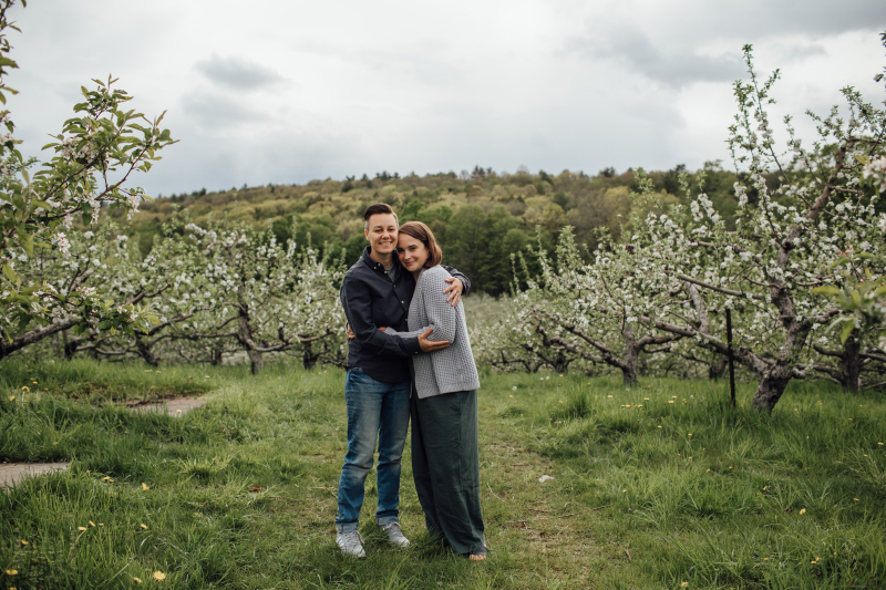 Two women pose together in an apple orchard in bloom with white flowers. The woman on the left has androgynous style and a short haircut. She is wearing a dark button down and blue jeans. The woman on the right has shoulder length brown hair and is wearing a grey knit cardigan sweater over a green jumpsuit. They are both looking at the camera and smiling.