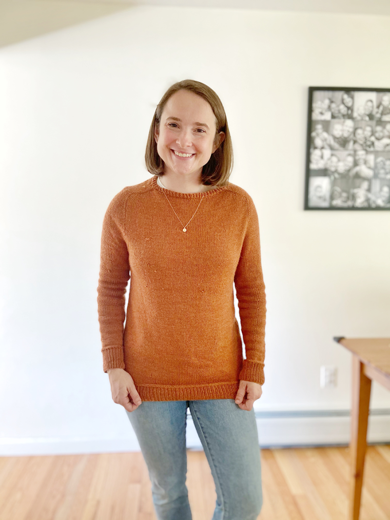 Hannah is wearing a rust-colored hand knit pullover sweater and standing in front of a white wall. She is smiling at the camera.