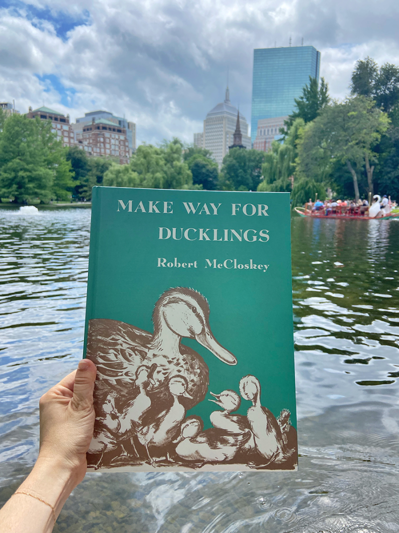 A copy of the children's book Make Way for Ducklings is held in front of the pond in the Boston Common park where swan boat rides take place
