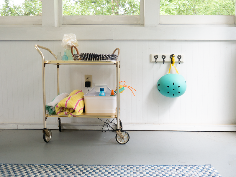 A gold bar cart has towels and toys on it. A wall hook has a turquoise helmet hanging from it.