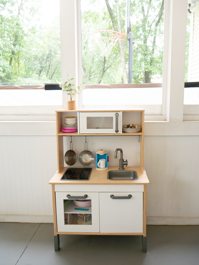 An Ikea children's play kitchen in an enclosed porch.